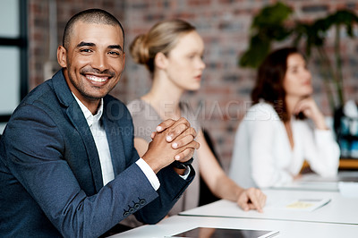 Buy stock photo Shot of a handsome young businessman sitting with his coworkers during a meeting in the office