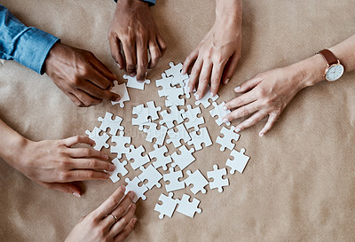 Buy stock photo High angle shot of an unrecognizable group of businesspeople using puzzle pieces to strategise in the office