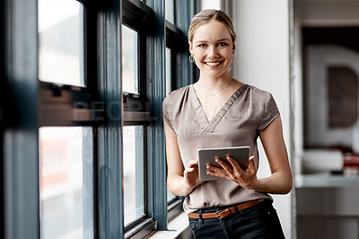 Buy stock photo Shot of an attractive young businesswoman standing alone in the office and using a digital tablet