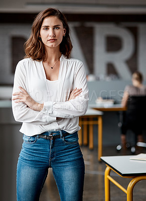 Buy stock photo Shot of an attractive young businesswoman standing alone in the office with her arms folded during the day