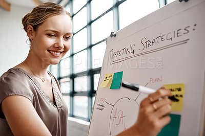 Buy stock photo Shot of a young businesswoman writing notes on a whiteboard in an office