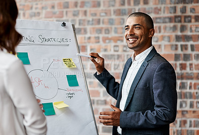 Buy stock photo Shot of a young businessman presenting notes on a whiteboard in an office