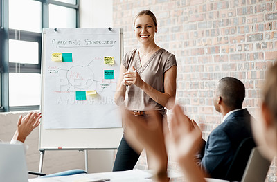 Buy stock photo Shot of a young businesswoman receiving applause during a presentation in an office