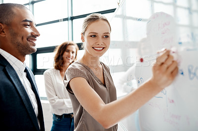 Buy stock photo Shot of a young businesswoman brainstorming on a whiteboard with her colleagues in an office