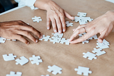 Buy stock photo Closeup shot of a group of unrecognisable businesspeople joining puzzle pieces together in an office