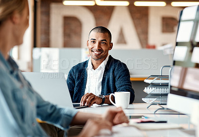 Buy stock photo Shot of a young businessman having a discussion with his colleague in a modern office