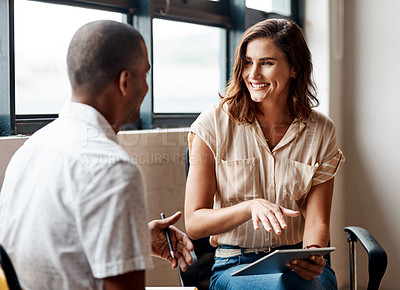 Buy stock photo Shot of a young businesswoman having a discussion with a colleague in a modern office