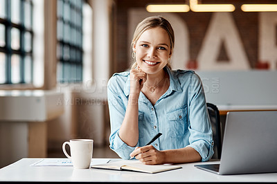 Buy stock photo Shot of a young businesswoman using a laptop in a modern office.