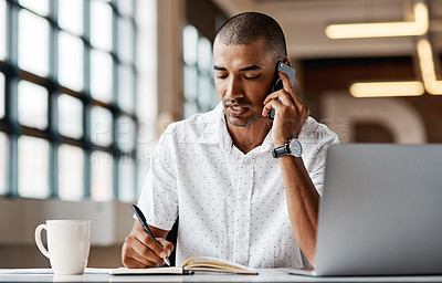 Buy stock photo Shot of a young businessman using a laptop, smartphone and making notes in a modern office