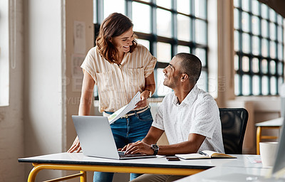 Buy stock photo Shot of a young businessman using a laptop with his colleague in a modern office
