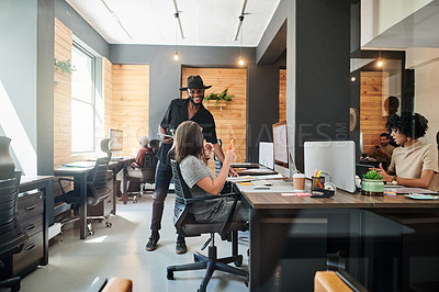 Buy stock photo Shot of a young businessman talking to a colleague in an office