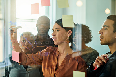 Buy stock photo Shot of a diverse group of businesspeople standing in the office together and using a transparent board during a meeting