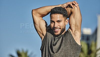 Buy stock photo Portrait of a sporty young man stretching his arms while exercising outdoors