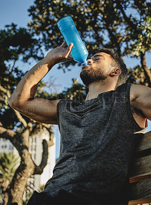 Buy stock photo Low angle shot of a sporty young man drinking water while exercising outdoors