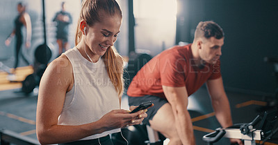 Buy stock photo Shot of a woman wearing earphones and using her cellphone during her workout at the gym
