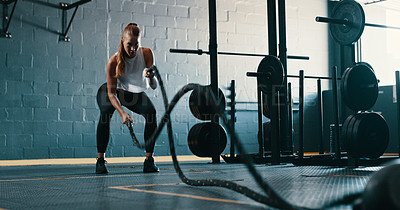 Buy stock photo Shot of a young woman working out with battle ropes at the gym