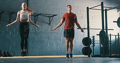 Buy stock photo Shot of two young people working out with skipping ropes at the gym