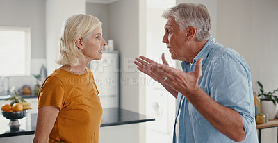 Buy stock photo Shot of a mature couple standing together at home and having an argument