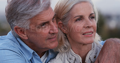 Buy stock photo Shot of a mature couple standing close together outside during the late hours of the day