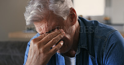 Buy stock photo Shot of a mature man sitting alone on the sofa at home and looking stressed