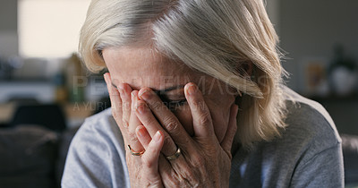 Buy stock photo Shot of a mature woman sitting alone at home and looking stressed