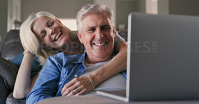 Buy stock photo Shot of a mature couple sitting in their living room together and watching a movie on their laptop