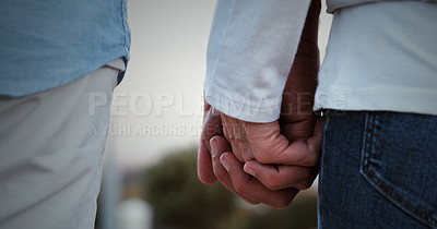 Buy stock photo Cropped shot of an unrecognizable couple holding hands and walking outside together