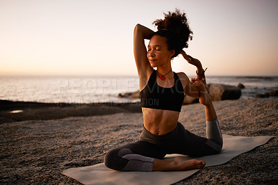Buy stock photo Full length shot of an attractive young woman practicing yoga on the beach at sunset