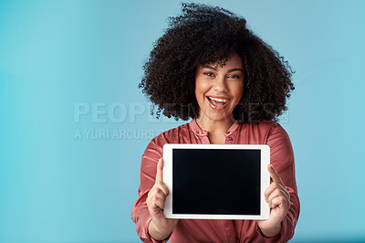Buy stock photo Studio shot of a young woman holding a digital tablet with a blank screen against a blue background