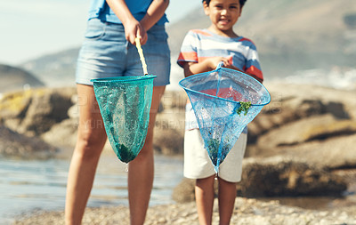 Buy stock photo Shot of a parent with their son at the beach holding fishing nets