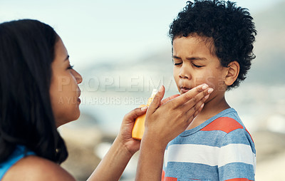 Buy stock photo Shot of a mother applying sunscreen to her son at the beach