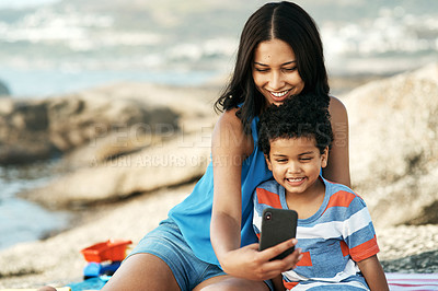 Buy stock photo Shot of a mother and her son taking selfies at the beach