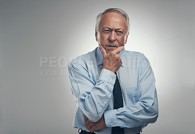Buy stock photo Shot of a senior businessman standing alone against a grey background in the studio and looking contemplative