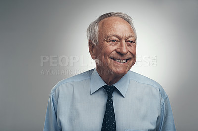 Buy stock photo Shot of a senior businessman standing alone against a grey background in the studio during the day