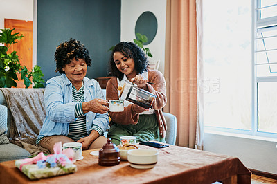 Buy stock photo Shot of a young woman having coffee with her elderly relative on the sofa at home