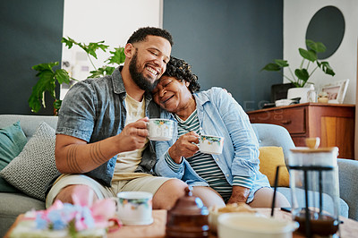 Buy stock photo Shot of a young man having coffee with his elderly relative on the sofa at home