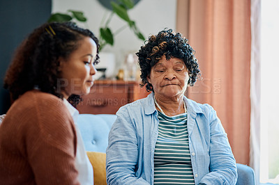 Buy stock photo Shot of an elderly woman sitting with her daughter on the sofa at home and not talking