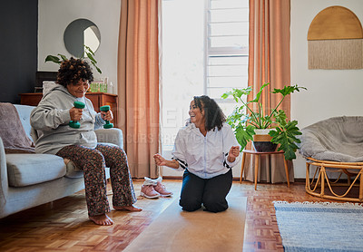 Buy stock photo Shot of an elderly woman working out with weights on the sofa with her daughter at home