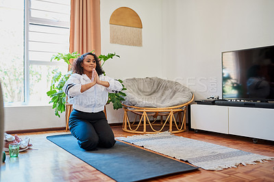 Buy stock photo Shot of a young woman meditating during her yoga routine at home