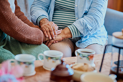 Buy stock photo Shot of a woman holding hands with her elderly relative while having coffee on the sofa at home