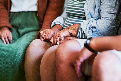 Buy stock photo Shot of an unrecognisable young man and woman holding hands with their elderly relative on the sofa at home