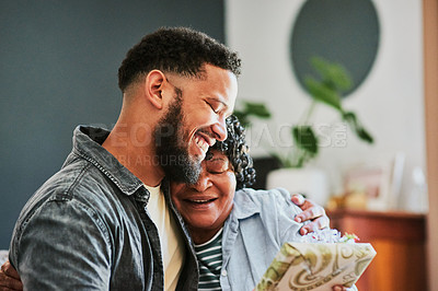 Buy stock photo Shot of a young man giving his elderly relative a present at home