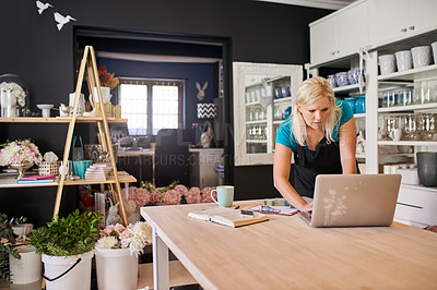 Buy stock photo Cropped shot of an attractive young woman using a laptop while working in her flower shop