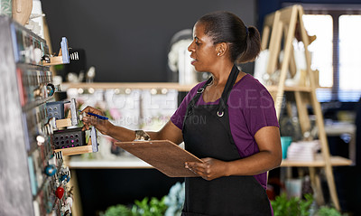 Buy stock photo Cropped shot of an attractive young woman standing with a clipboard while doing stock take in her flower shop