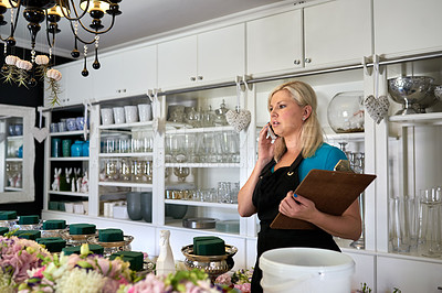 Buy stock photo Shot of a young woman on a business call at her job in a floral store