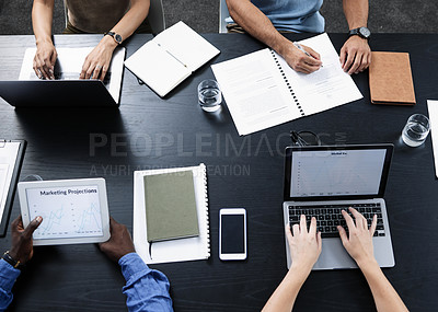 Buy stock photo Shot of a team of businesspeople using various tech devices in their office