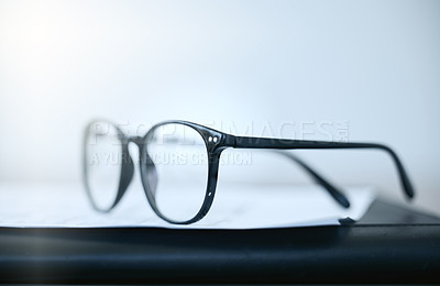 Buy stock photo Shot of a pair of glasses lying on a desk in an empty office during the day