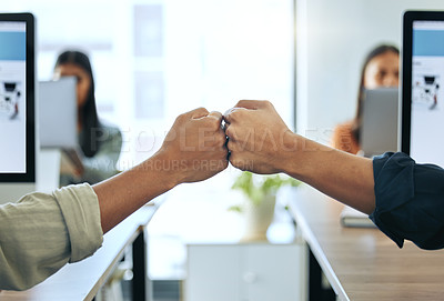 Buy stock photo Cropped shot of two unrecognizable businesspeople sitting together in the office and giving each other a fist bump