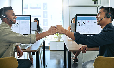 Buy stock photo Shot of two handsome salesmen sitting together in the office and giving each other a fist bump