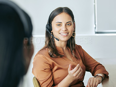 Buy stock photo Shot of an attractive young saleswoman sitting in the office with a colleague and wearing a headset